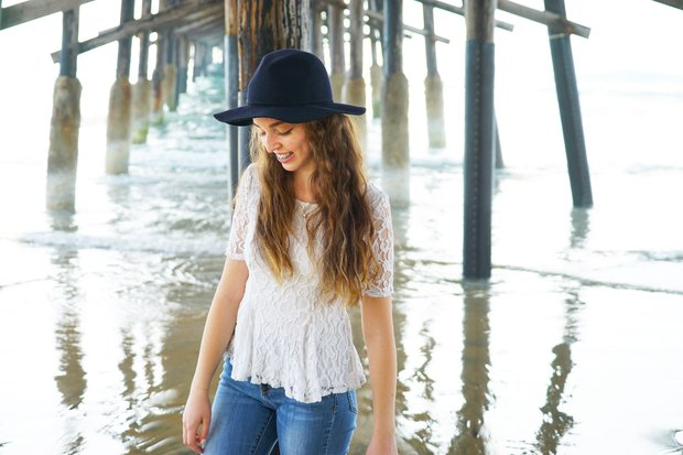 girl smile black hat jeans white lace beach braces wavy hair
