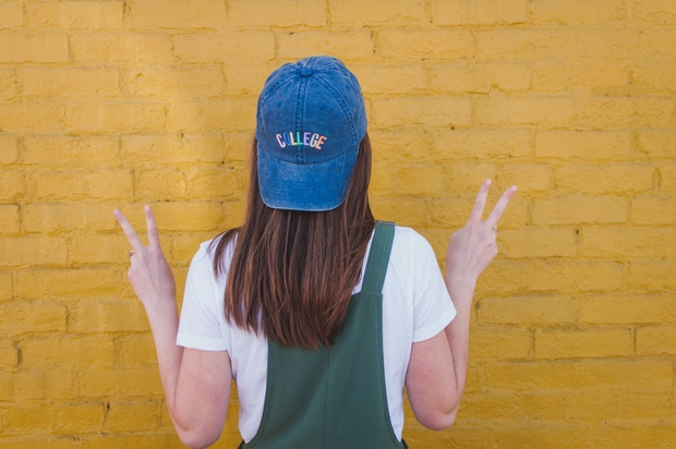 girl with blue college cap yellow wall