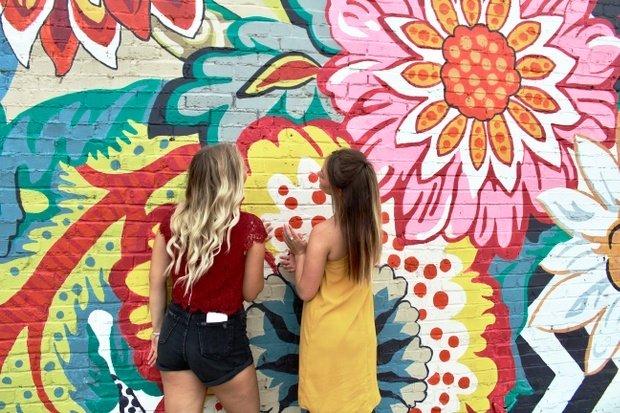 two girls friends long hair blonde and burnette flower mural