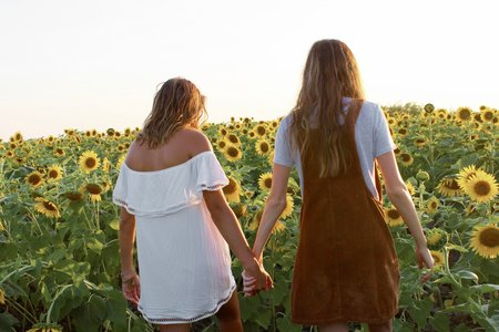 friends holding hands sunflower field dresses summer