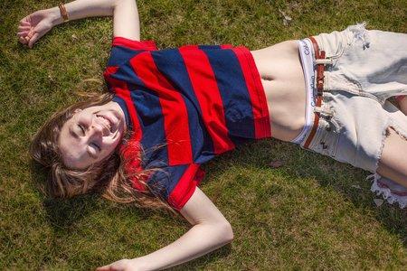 girl in sun in g rass ripped jeans