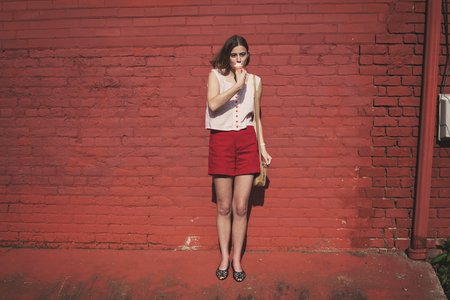 girl in front of red brick wall eating ice cream 1