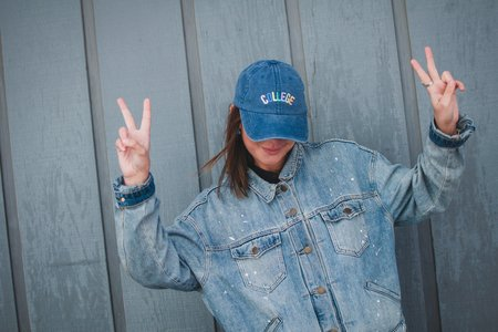girl with jean jacket and collge hat peace sign