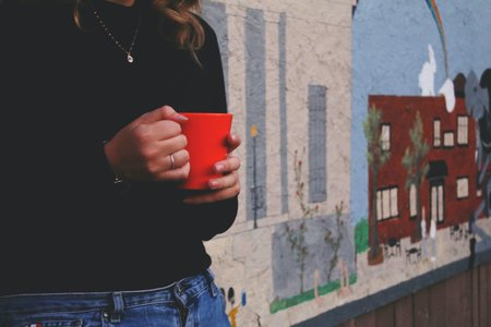 The Lalagirl Holding Mug In Front Of Mural