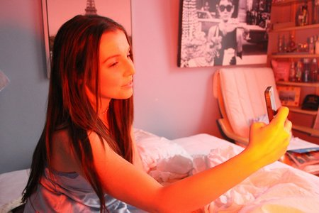 Anna Schultz-Girl Taking Selfie In Bed Orange Lighting