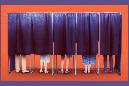 People standing inside of blue material voter polls