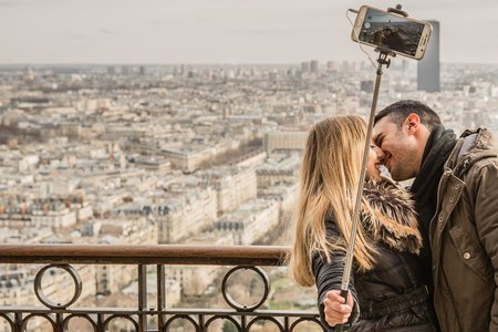 Man Kissing Woman Holding Selfie Stick
