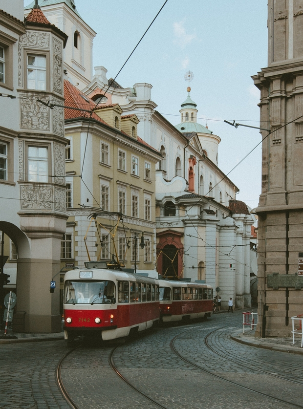 Red Tram Passing Between Concrete Buildings