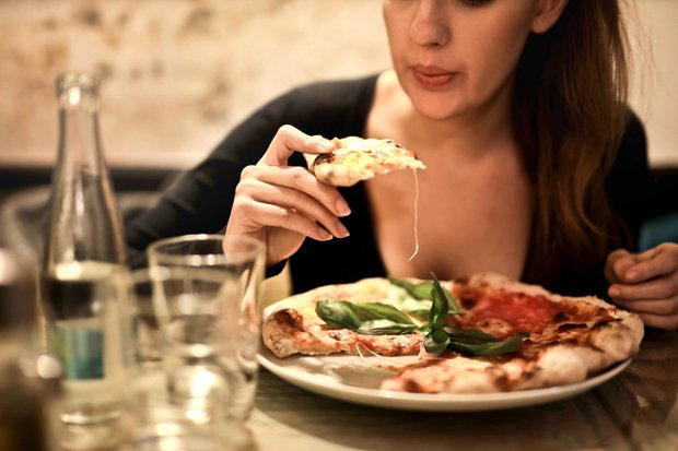 Woman Holds Sliced Pizza Seats By Table With Glass