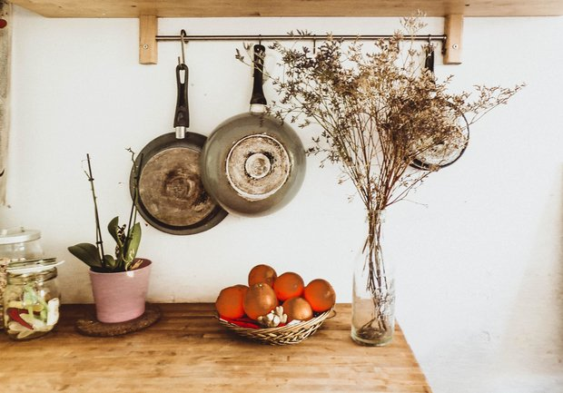 Two Gray Frying Pans Hanging On Wall