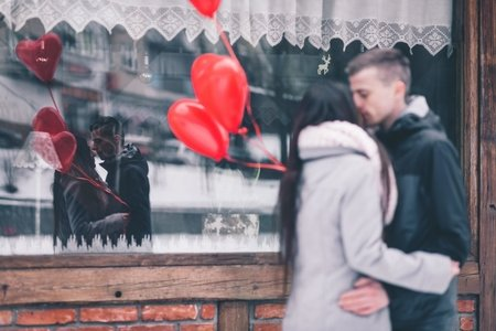 man and woman kissing with balloons