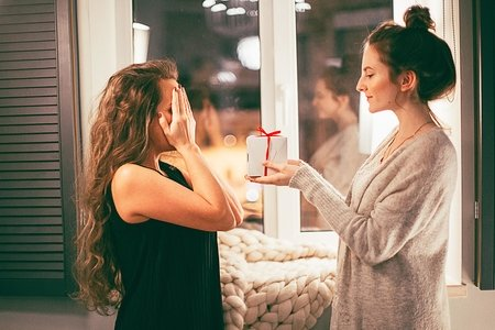 woman giving gift to another woman