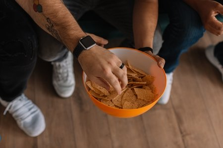man's hand grabbing a chip out of an orange bowl