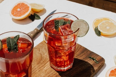 2 drinks in clear glasses surround by sliced fruit