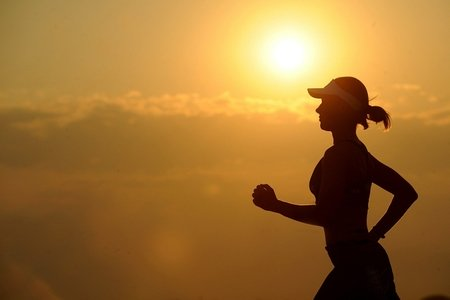Woman running with a sunset in the background