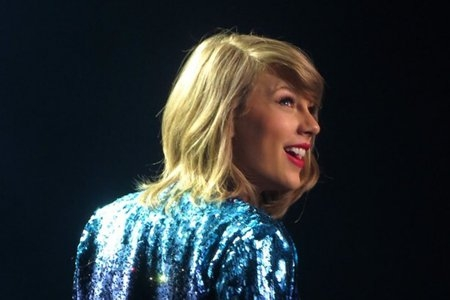 Taylor Swift on stage in colorful jacket