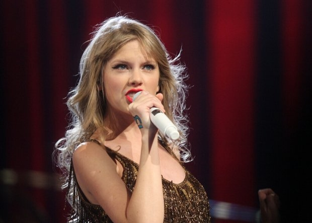 Taylor Swift on stage singing in a gold sequin dress