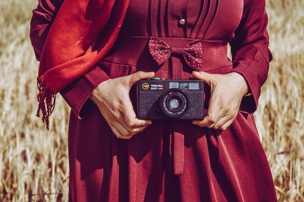 person wearing red holding camera