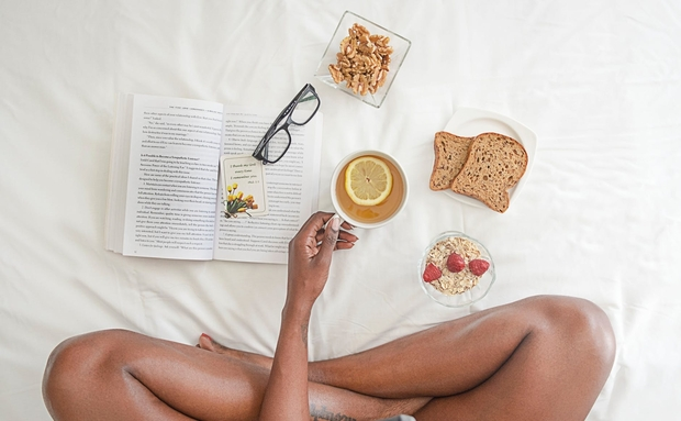 Woman holding a white mug with breakfast food and a book open on a bed