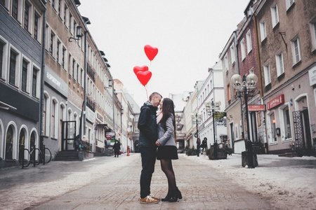 couple kissing in the street with heart balloons in the background
