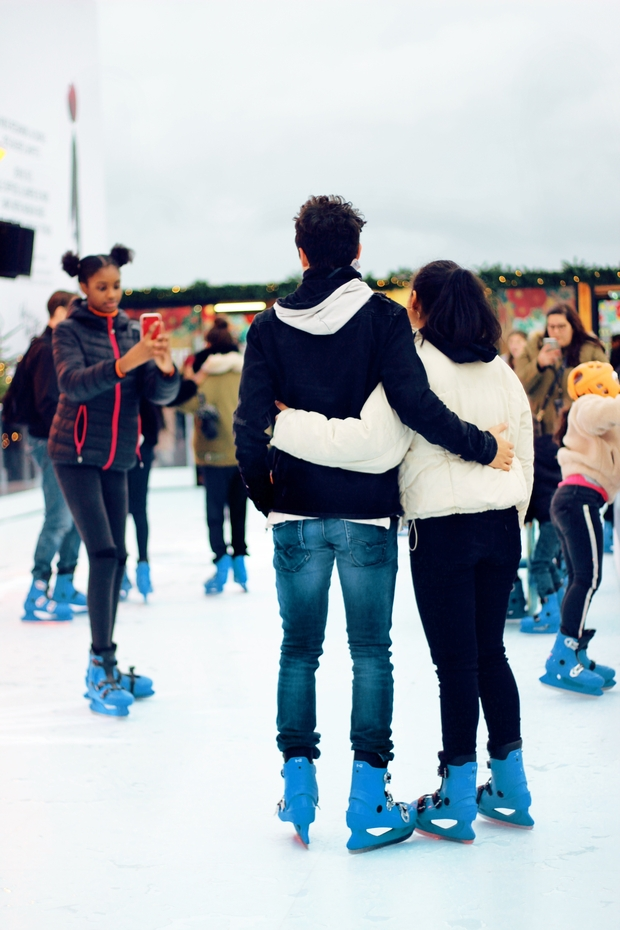 girl taking picture of a couple ice skating