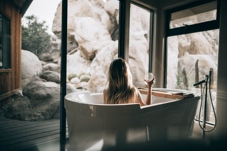 girl taking bubble bath while looking at landscape