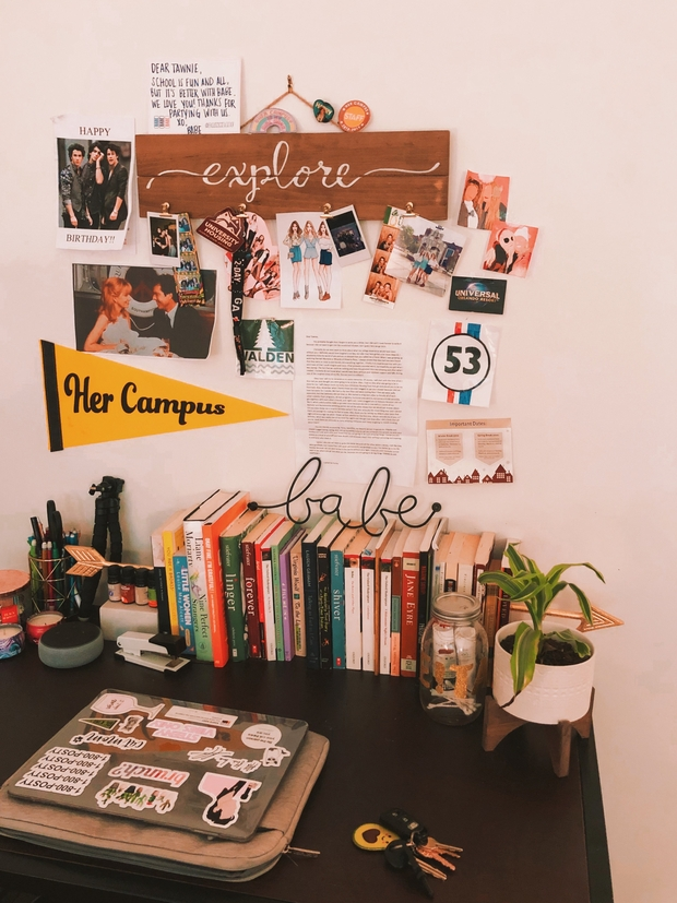 A desk in a bedroom with keepsakes and decor hanging above it