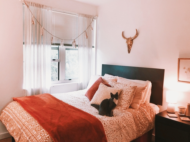 A bed that is decorated with burnt orange tones next to a window with sheer curtains