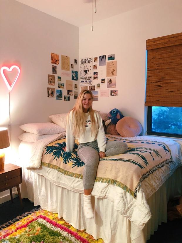 Ingrid sitting on her bed