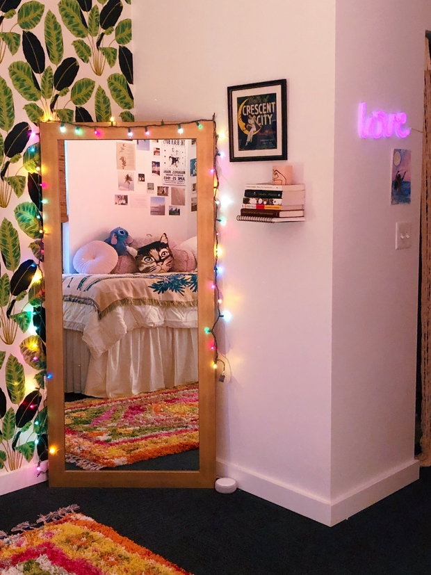 Corner of Ingrid's bedroom that shows leafy wallpaper and a large mirror with colorful lights