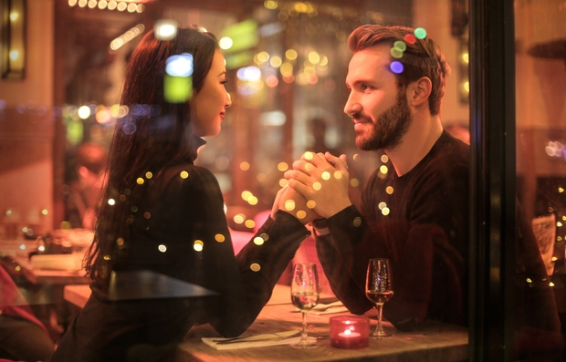couple seen holding hands through the window at a table with two glasses of wine on the table
