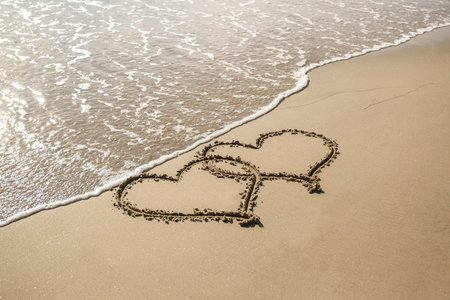 two hearts in sand on a beach