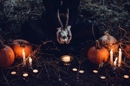 A witch sits among pumpkins and candles holding a jackalope skull