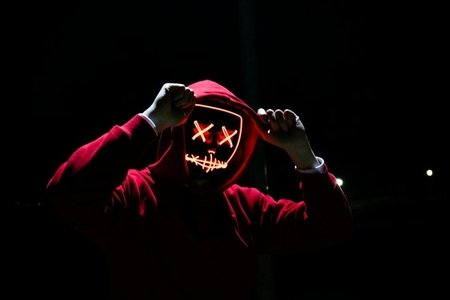 A person in a red hoodie holds his hands to the hood, and is wearing a red horror movie mask.