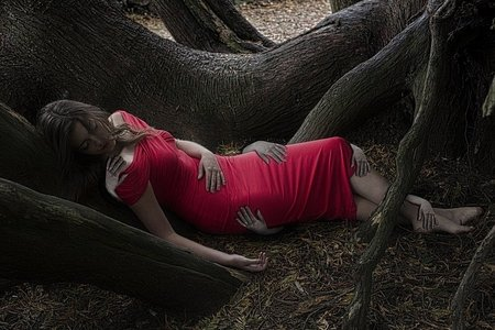 A woman is asleep among tree roots, phantom hands hold parts of her body