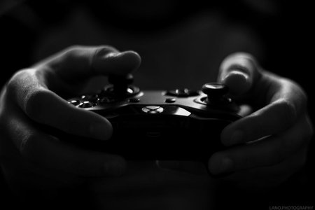 Black and white photo of hands holding an X-box controller