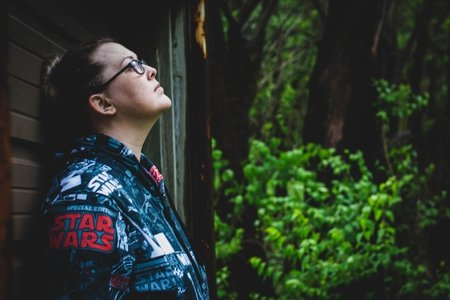 A female star wars fan in glasses leans against a wall near some trees