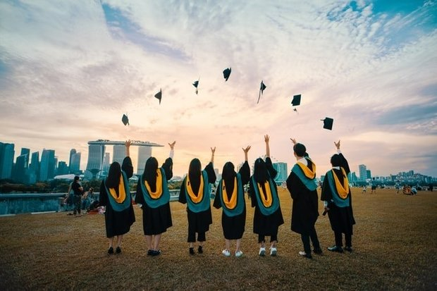 seven graduates throwing their hats