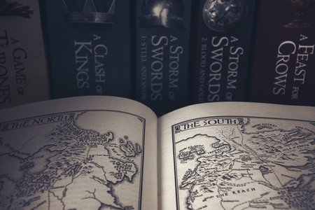 A book is open to pages of drawn maps, the background is a shelf containing the Game of Thrones books