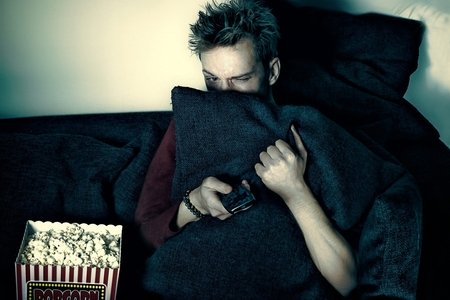 A man is sitting on a couch, next to popcorn in the dark, hiding behind a pillow