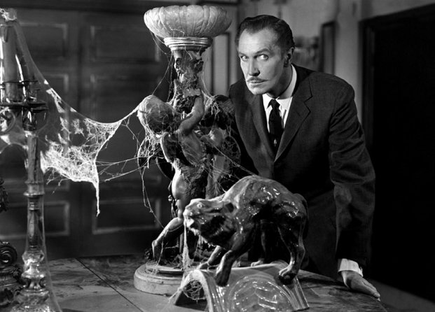 A black and white photo of Vincent Price next to a table of vintage objects covered in exaggerated cobwebs