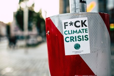 "A white and red trash can/bin has a sticker on it that says ""F*CK Climate Crisis"""