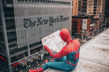 A man in a spiderman costume reads the newspaper on top of a building