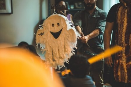 A Halloween Party, someone is hitting a ghost pinata.
