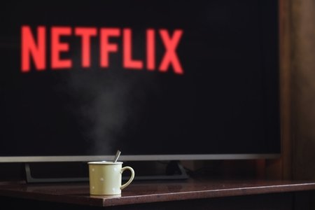 "A fuzzy screen in the back ground might say ""netflix"" but the image's selective focus is on a mug of some sort."