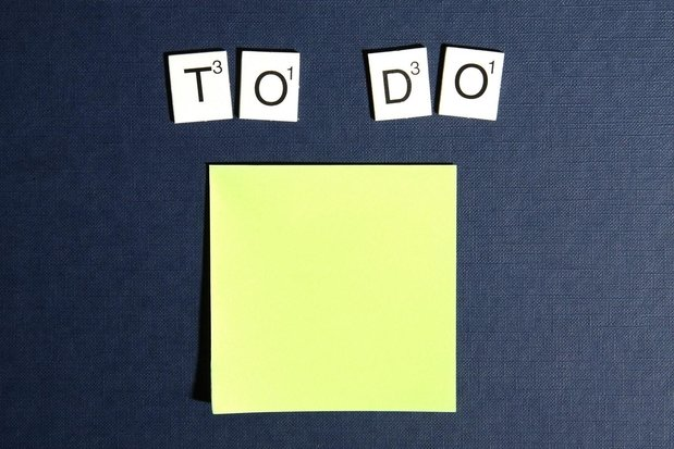 "Scrabble tiles spell out ""To Do"" on a blue background above a yellow sticky note"