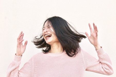 smiling woman in pink sweater
