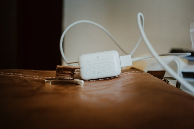 while charger and cord lying on top of leather bag