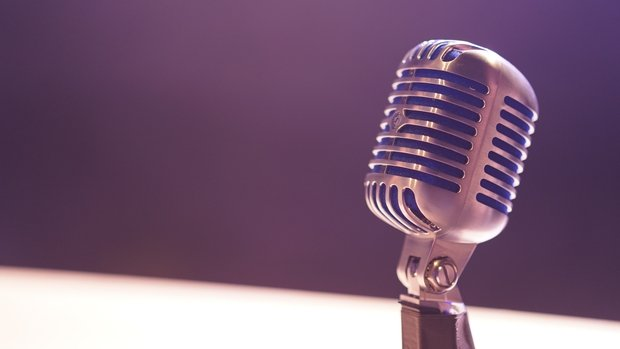 old fashioned crome microphone in front of a purple background