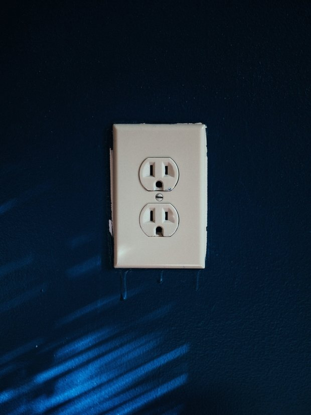 white wall outlet on a blue painted wall
